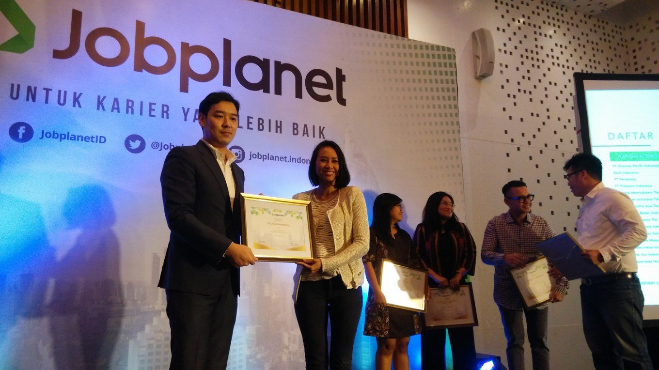 Jobplanet regional director Kim Kinan (left) hands an award to Monica Oudang, the human resources director of Go-Jek Indonesia on Dec. 15 in Jakarta. Aside from Go-Jek, other start-up companies also received awards including Blibli, Sale Stock and MatahariMall. (JP/win)