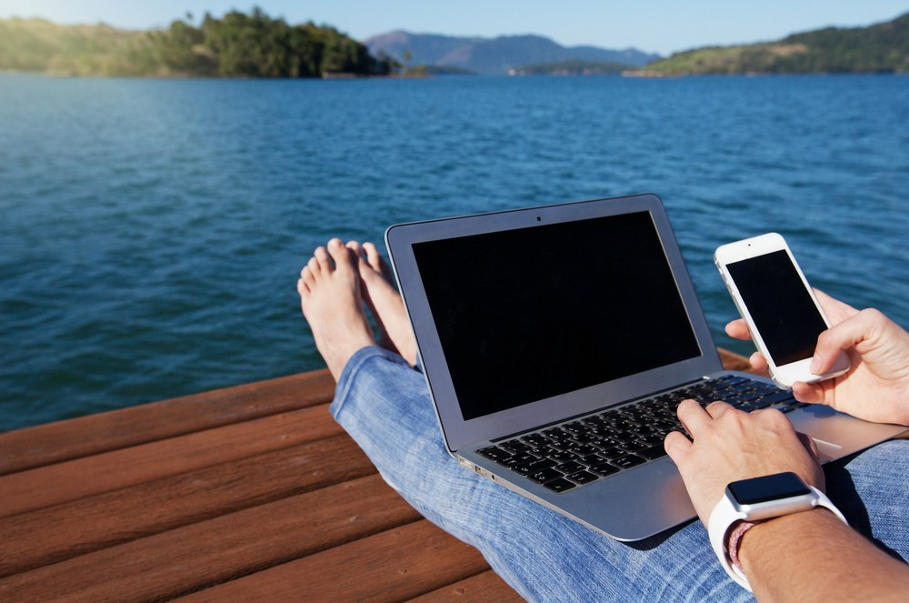 A young woman works with a laptop on a pier, also using smartwatch and a smartphone. (Shutterstock/File)