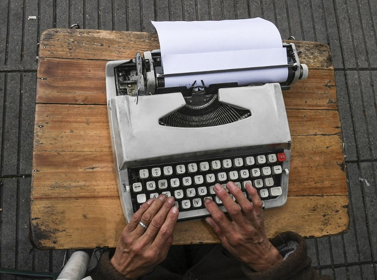 Street clerk Candelaria Pinilla,63, types a letter on her typewriter, in front of the district taxing office in Bogota, on April 9, 2018 Street clerks are experts in filling out forms, documents and even in typing letters, to help their clients with paperwork. (AFP/Luis Acosta)
